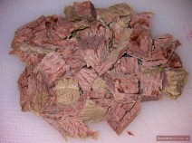 Remove cooked onion and bay leaves. Strip meat off bones and finely chop it.