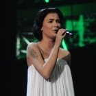 Anastasia Prikhodko sings on stage wearing a white full length dress at the ESC in Russia