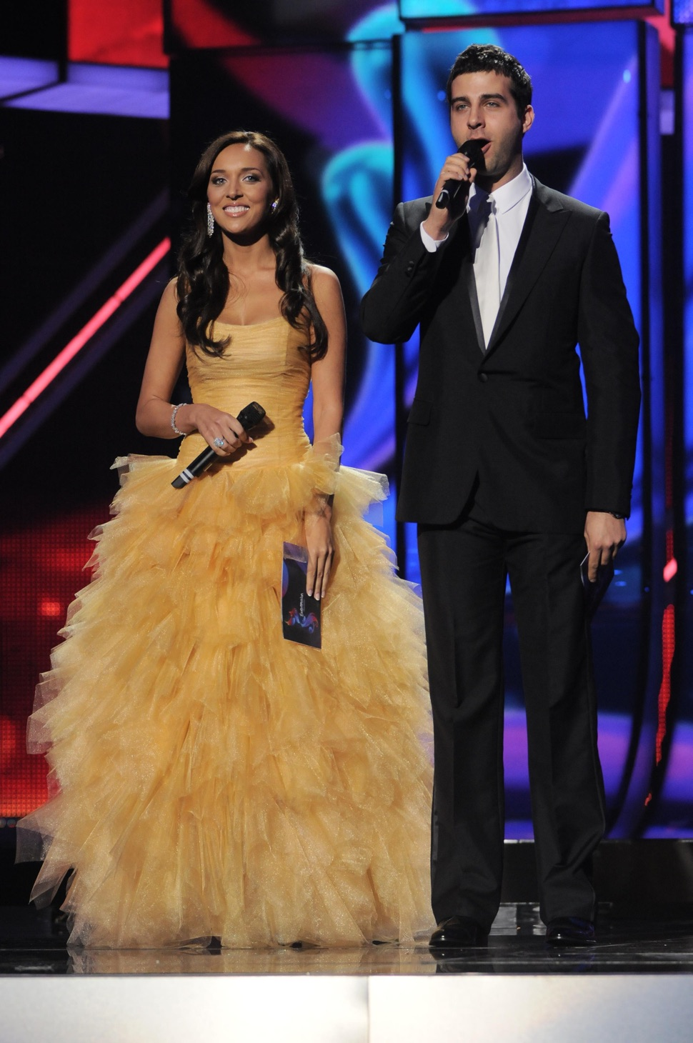 Alsou in yellow dress smiling and Ivan Urgant in smoking, on stage, both with microphones