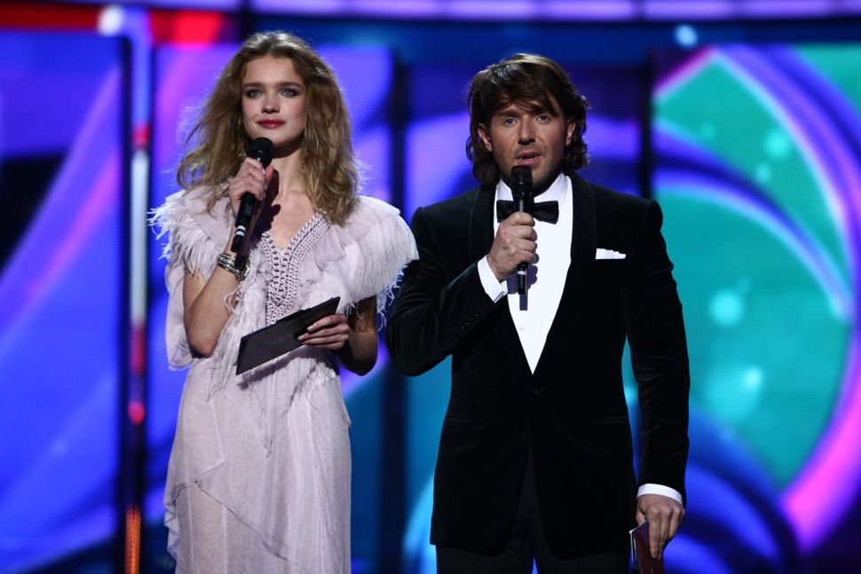 Natalia Vodianova in white dress and Andrei Malakhov in smoking, on stage, both with microphones