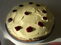 Покрытый белым кремом и украшенный капельками красного варенья торт Трухлявый пень
