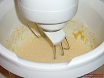 Яйца взбитые с сахаром в белой миске кухонного комбайна
