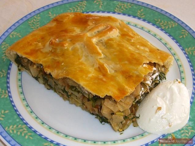 Кусок пирога с начинкой из капусты и свежей зелени