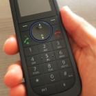Рука держит чёрный телефон с кнопочным набором