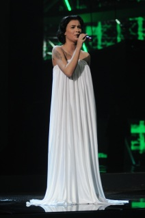 Анастасия Приходько поёт на сцене в длинном белом платье