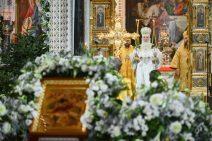 Der Patriarch im weißen festlichen Gewand mit Kerzen hinter der Ikone der Geburt Christi