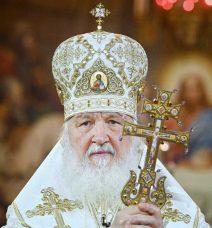 Porträt vom Patriarchen mit festlicher weiß-goldener Kopfbedeckung und Kreuz in den Händen