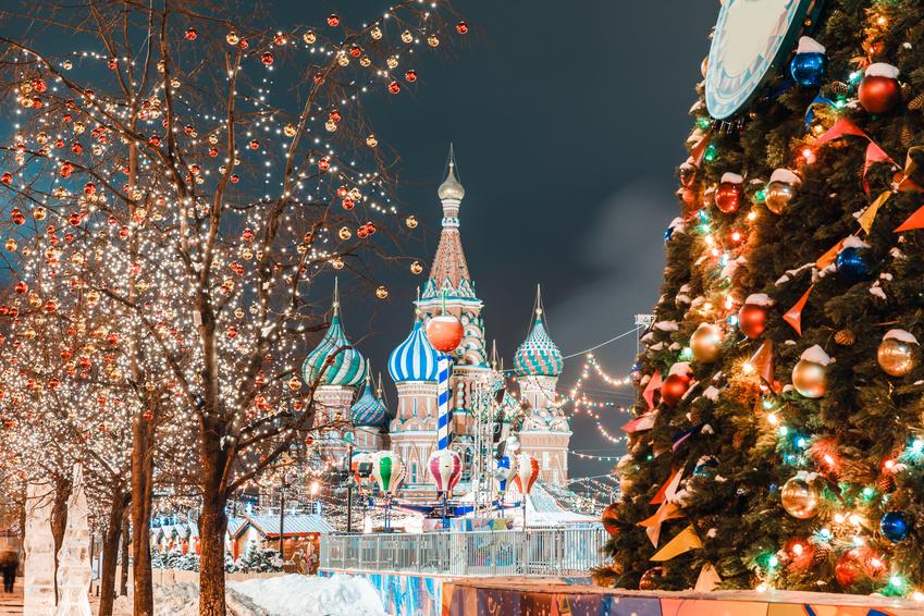 Roter Platz in Moskau mit Silvester und Weihnachtsdekoration. Blick auf die Basilius-Kathedrale, geschmückter Tannenbaum, Bäume mit roten und goldenen Kugeln.