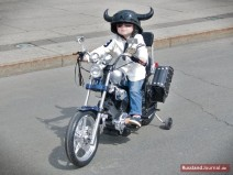 Kleiner Junge mit Helm auf Motorrad