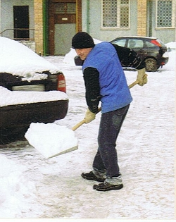 Mann in blauer Weste schaufelt Schnee im Hof, ein Foto aus dem MOCT 1 Russisch Lehrbuch für Anfänger
