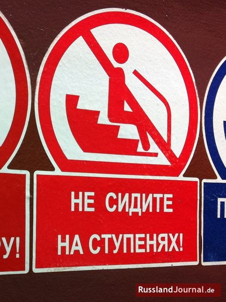 Hinweisschild in Metro auf Russisch: Не сидите на ступенях! = Sitzen Sie nicht auf den Stufen!