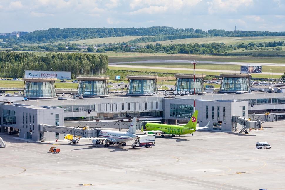 Renoviertes Flughafengebäude mit fünf Türmen und zwei Flugzeuge davor