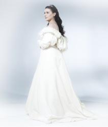 Cecilia Bartoli in einem langen weißen Mantel mit langen offenen Haaren und Krönchen.