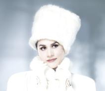 Portrait von Cecilia Bartoli mit weißer Fellmütze und weißem Mantel mit hohem Kragen.