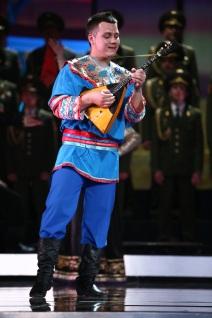 Man in blauer russischer Nationaltracht spielt Balalaika vor dem Chor des Alexandrow Ensembles der Russischen Armee