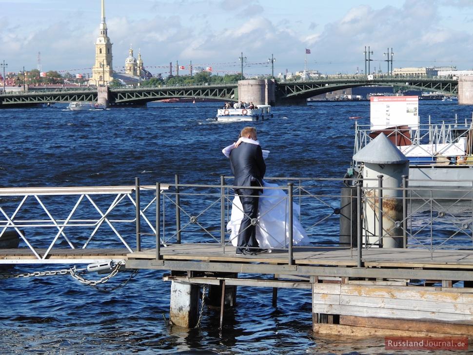 Brautpaar umarmt sich auf einem Holzsteg an der Newa vor Peter-Paul-Festung in St. Petersburg
