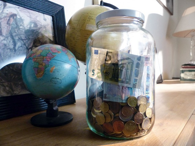 Sparglas mit Euro-Münzen und zwei Geldscheinen
