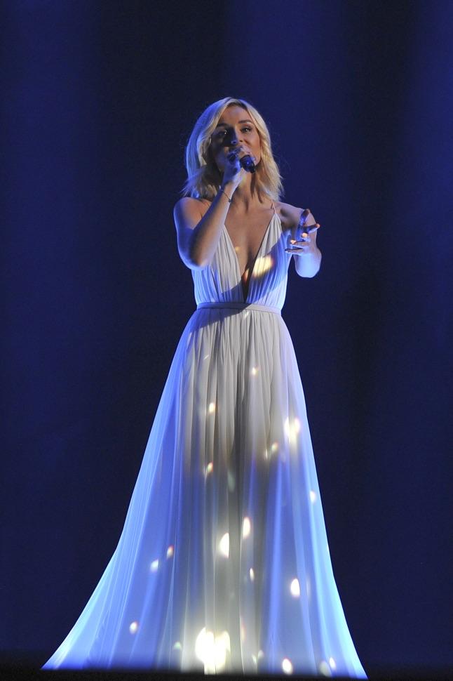 Polina Gagarina singt im weißen Kleid auf dunkelblauen Hintergrund