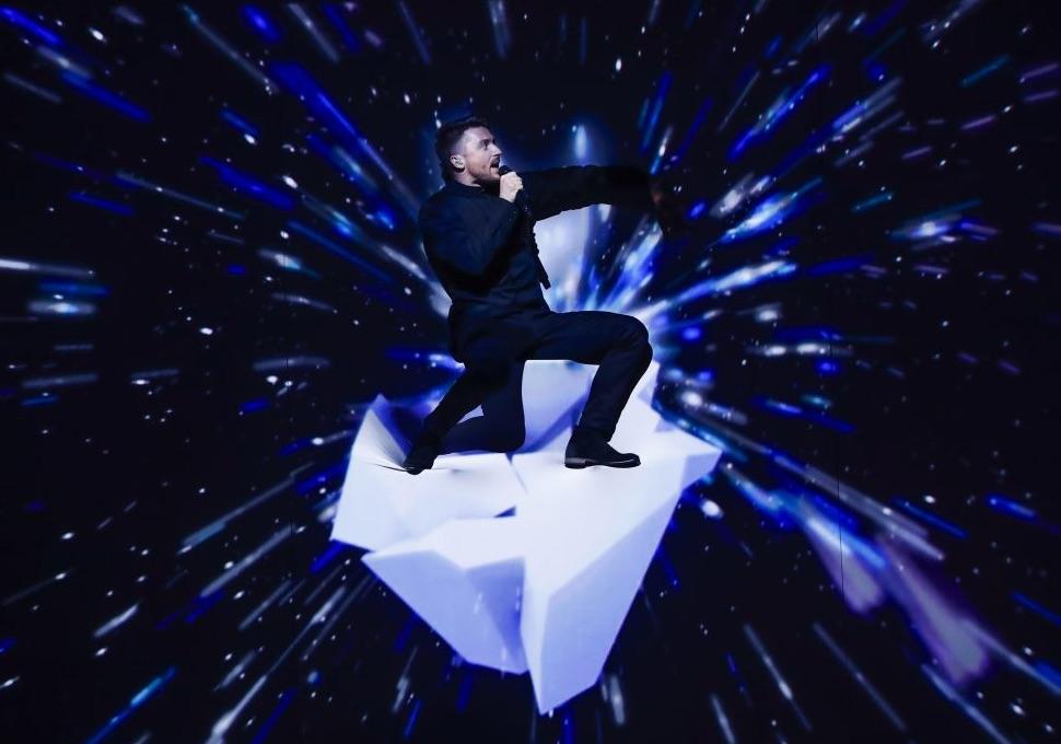 Sergey Lazarev im dunklen Anzug singt kniend auf einem Knie