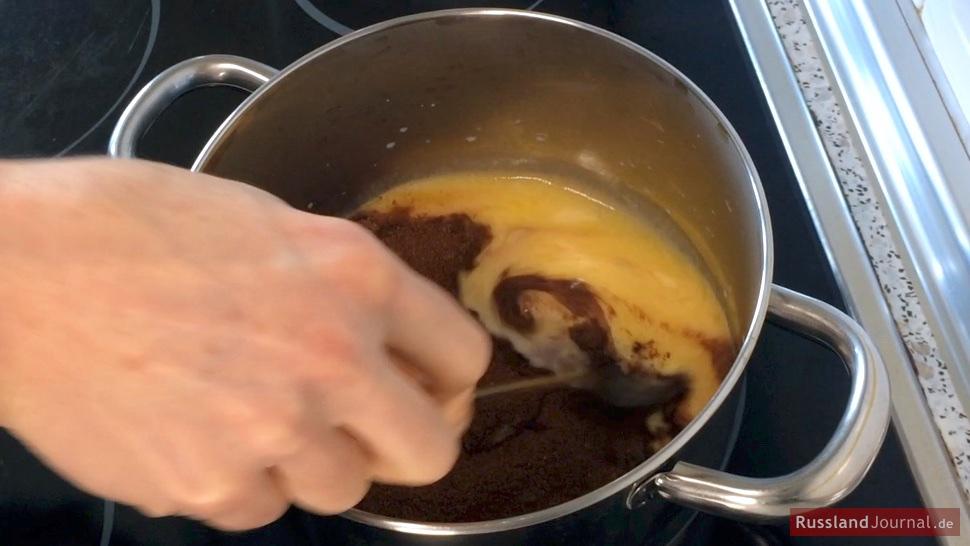 Butter und Kakao-Zucker-Mischung wird im Topf unter die Milch gerührt.