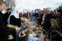 Der Patriarch von Russland weiht auf einem langen Tisch aufgestellte Osterspeisen