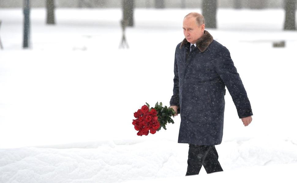 Putin mit einem Rosenstrauß im Winter am Piskarjowskoje-Gedenkfriedhof anlässlich des 75. Jahrestages des Durchbruchs der Leningrader Blockade
