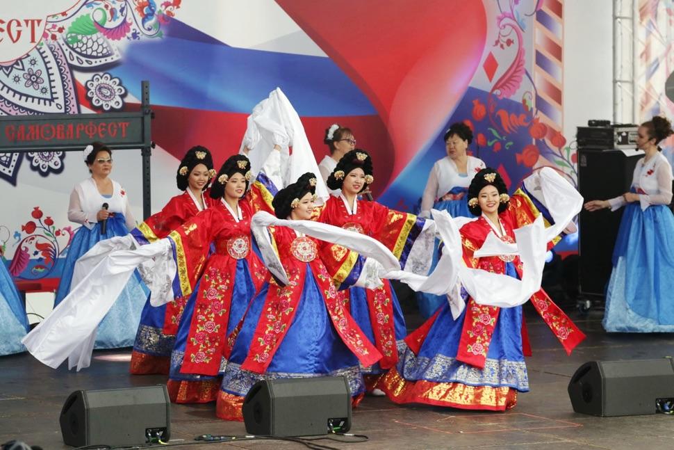 """Frauen in weiß-blau-roten Kleidern tanzen ein Volkstanz beim """"Samowarfest"""" auf WDNCh"""