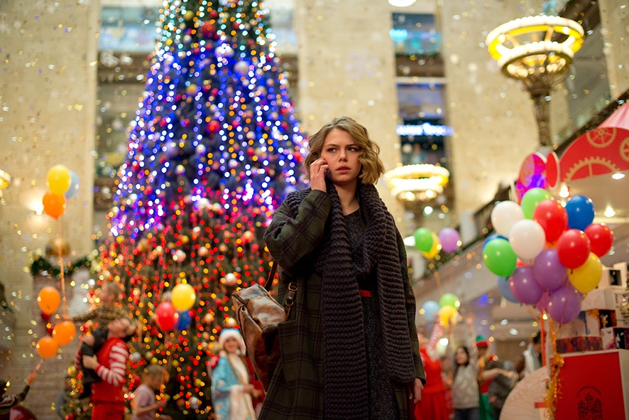 Mascha mit Handy im Kinderkaufhaus vor Weihnachtsbaum