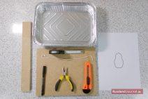 Aluschale, Metermaß, Faden, Teppichmesser, Zange, Stift, Latte, Holzunterlage